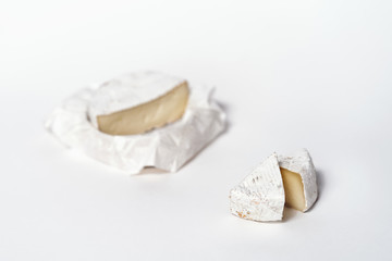Cheese camembert or brie sliced on white background. Menu design restaurant. Top view design photo. Cheese in white paper.