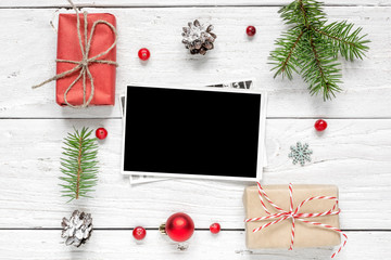 blank photo card in frame made of fir tree branches, decorations and gift boxes