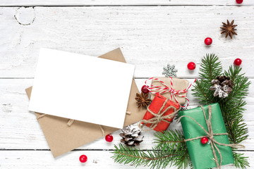christmas blank greeting card and envelope with fir tree branches, red berries, pine cones and gift boxes