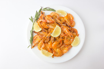 Fried prawns on a white plate. Shrimp fried in oil with garlic and lemon on a plate.