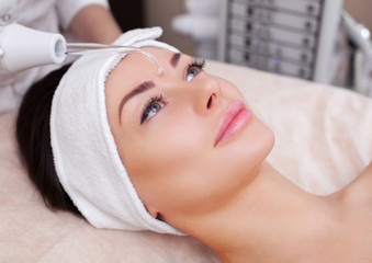 The cosmetologist makes the procedure electrotherapy  of the facial skin of a beautiful, young woman in a beauty salon.Cosmetology and professional skin care.