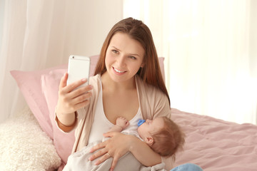 Young mother taking selfie with baby at home