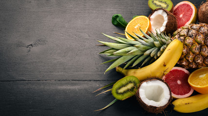 Fresh Tropical Fruits. Pineapple, coconut, kiwi, orange, pomegranate, grapefruit. On a wooden background. Top view. Free space for text.