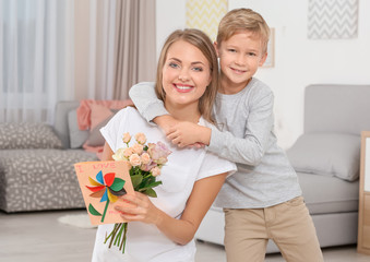 Young woman with her little son and  gifts for Mother's Day at home