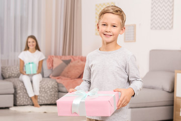 Cute little boy with gift for Mother's Day at home