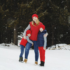 Mother and her two sons having fun in winter in snow forest