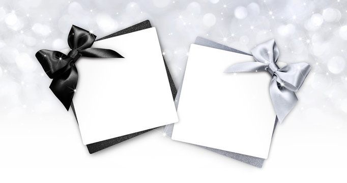 gift cards with black and silver ribbon bow Isolated on christmas bright lights background