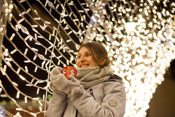 woman holding mug with mulled wine at christmas market
