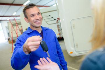 Mechanic handing key to client