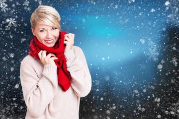 lächelnde junge Frau im Winterpullie und Schal vor winterlichem Hintergrund