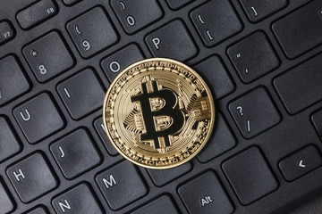 Golden bitcoin on keyboard, top view
