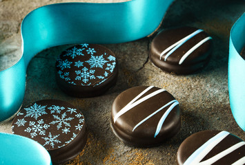 Chocolate-covered cookies with seasonal decorations and blue ribbon on stone background