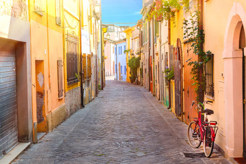 Narrow street of the village of fishermen San Guiliano with colorful houses and a bicycle in early morning in Rimini, Italy