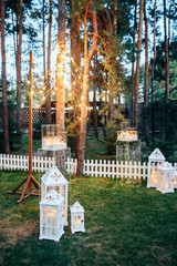 Decorated area with white wooden candle lamps and flowers on the grass