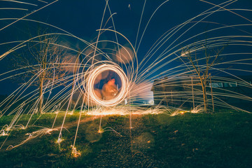 Steel wool photography. Bright sparkles flying in circles and hitting a green grass making fire explosions. Ring of fire.