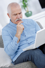 handsome old man casual style is using a laptop