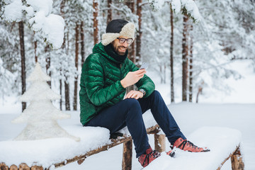 Smiling positive male wears warm winter clothes, reads message on mobile phone, spends free time in calm atmosphere outdoors in winter forest, enjoys fresh air. People, rest, technology concept