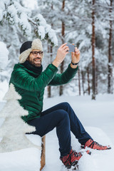 Vertical portrait of pleasant looking male makes photo with smart phone, makes shots of beautiful winter landscapes, enjoys nature and frozy weather, has pleasant smile. People, technology concept