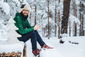 Photo of cheerful male types messages on smart phone looks directly into camera, sits in white winter forest, smiles happily, enjoys communication, watches video, admires landscapes