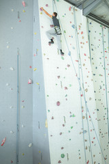 wide view of male climbing on an indoor climbing wall