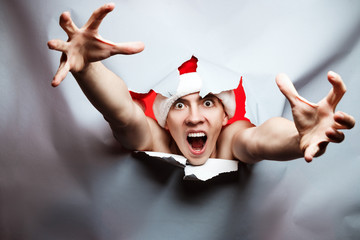 Christmas New Year concept, Stylish Crazy guy santa hat breaks through paper and try to catch something with angry face, with place for text, concept of buying and discounts on holidays