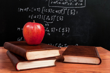 Apple on books on a wooden desk during math class in the classroom