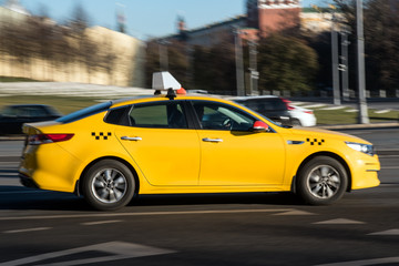 Yellow taxi car in motion on city street