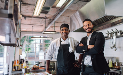 Zelfklevend Fotobehang Restaurant Restaurant owner with chef in kitchen