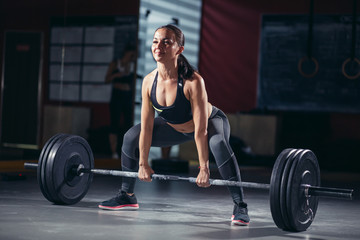 Extreme workout: muscular female athlete starting barbell exercise standing in squat stance. The concept of sport and a healthy lifestyle, control over their body. Cross fit.