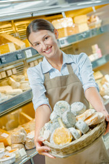 Deli worker holding basket of cheeses