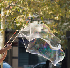 Large Iridescent Bubble shimmering in the sunlight that is being formed with soapy water, bamboo sticks and string. The arms of an adult and child are seen holding the sticks.