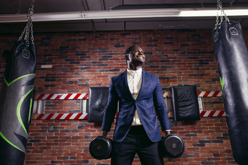 Sexy african man in classic suit working out with dumbbells in gym.