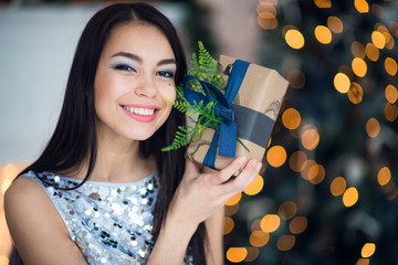 Beautiful excited smiling young woman with present gift feeling happy near christmas tree. Close-up portrait
