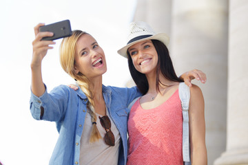 cheerful tourist female friends taking photos of themselves
