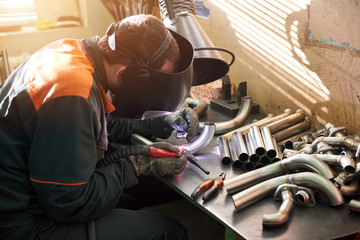 Welder is working. Man welding small pipe.