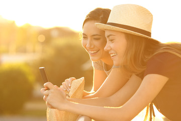 Two friends watching on line content at sunset
