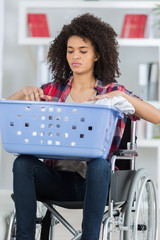 young disabled woman on wheelchair doing laundry