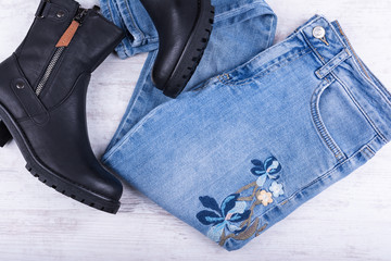 Blue jeans and female black leather shoes on white wooden background. Women's fashion clothes.