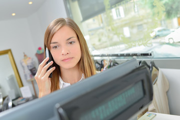 Young shop worker manning the till