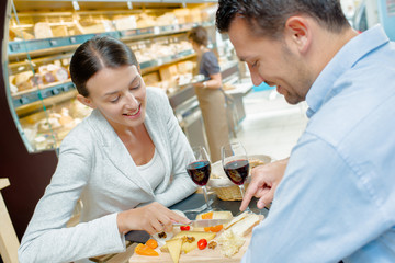 couple tasting food in supermarket