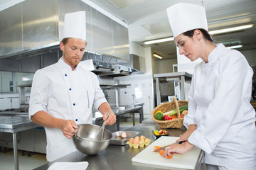 a male and female chef posing in restaurant kitchen