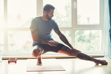 handsome sporty man doing exercise at home
