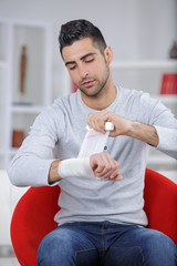 man bandaging his wrist