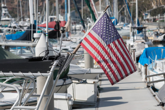 Small American flag on boat docked in marina. Wooden post. Shallow depth of field. Blurred background.