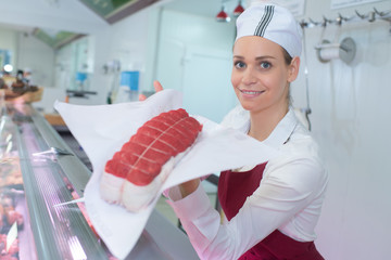 Female butcher showing lean joint of meat