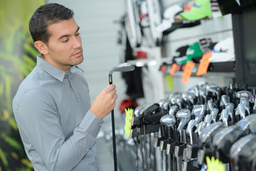 man inspecting the golf clubs