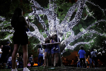 Woman takes a picture of a family  near trees decorated with Christmas lights at Ibirapuera Park in Sao Paulo