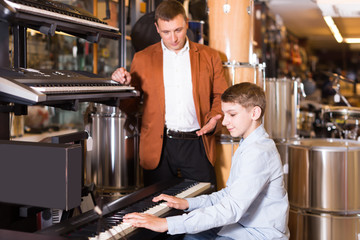 Brunette boy and father deciding on synthesizer