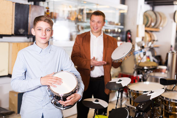 Boy and father choosing best drum