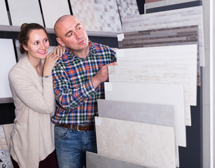 middle class family selecting  kitchen tile in store